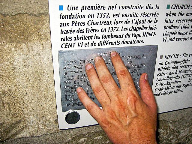 Mains d'une personne lisant un texte en braille lors de la visite d'un monument historique