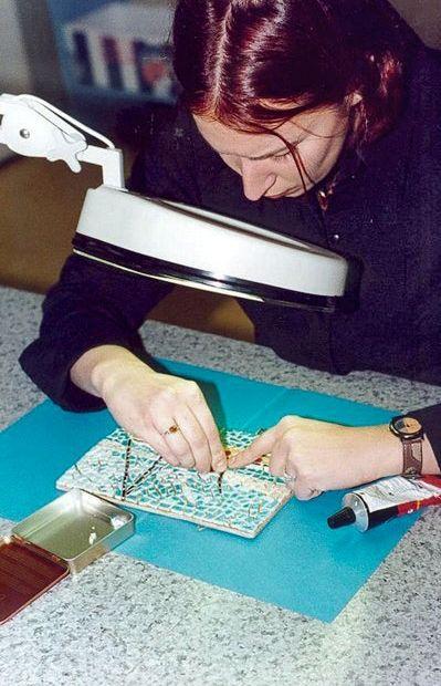 Femme effectuant un travail de mosaïque avec une loupe éclairante