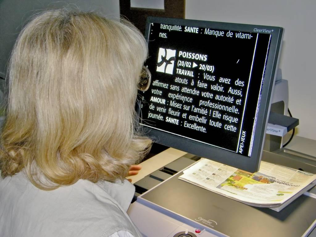 Femme lisant son horoscope dans un journal à l'aide d'un téléagrandisseur
