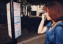 Jeune femme à l'arrêt d'un bus lisant les horaires grâce à un monoculaire