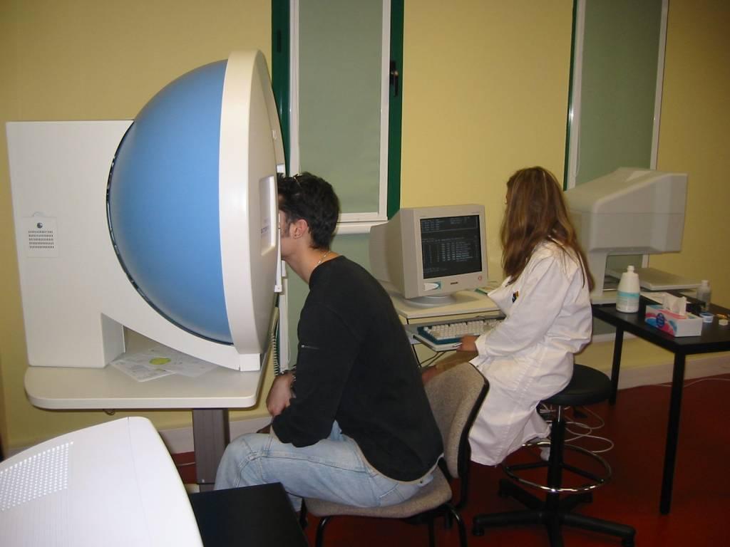 Examen du champ visuel d'un homme par un orthoptiste